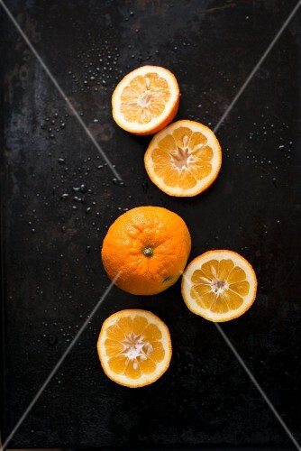 Seville oranges, whole and halved on a black surface