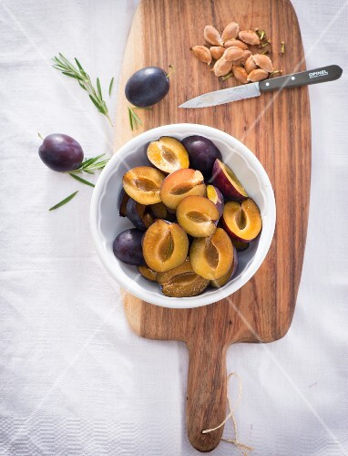 Pitted damsons in a bowl on a wooden board