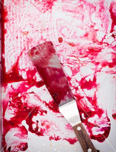 A baking tray and a palette knife smeared with plum juice