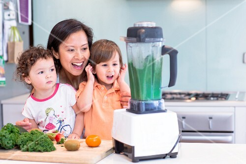 A woman mixing a smoothie for little girls in a kitchen