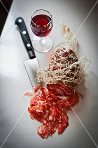 Rosette sausage in a net with a glass of red wine and a knife