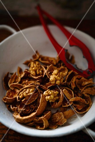 Cracked walnuts and a nutcracker in a bowl