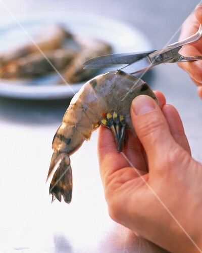 A prawn being cut open with a pair of scissors
