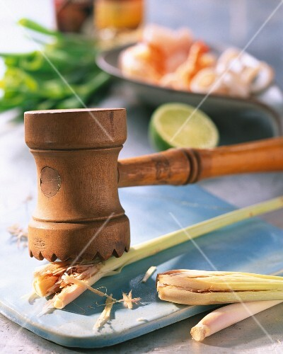 Lemongrass being crushed with a kitchen hammer