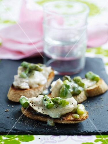 Crostini topped with fish and green asparagus