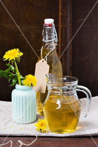 Dandelion syrup in a glass jug and a bottle
