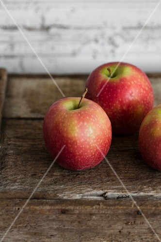 Three Pink Lady apples on a wooden crate