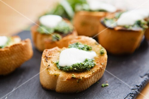 Crostini topped with pesto and mozzarella