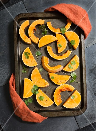 Butternut squash wedges with coriander on a baking tray ready for roasting