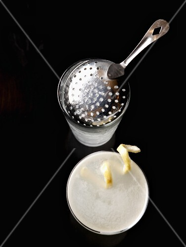 Lemon Drop cocktail with lemon zest, a shaker and bar sieve