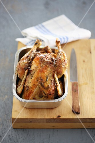 Roast chicken in a metal dish on a wooden chopping board
