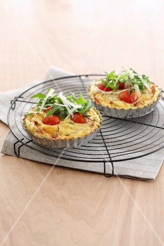Mini tomato quiches with ham and rocket on a wire rack