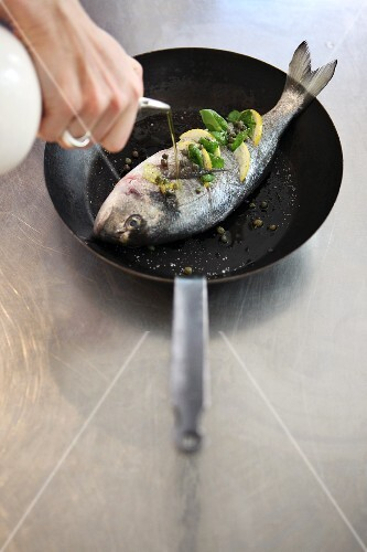 A fish larded with herbs and lemons being drizzled with oil in a pan