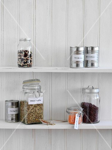 Jars of legumes and tins of preserves on a kitchen shelf