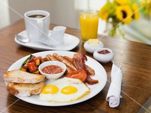 An English breakfast with fried eggs, sausages, bacon and bread
