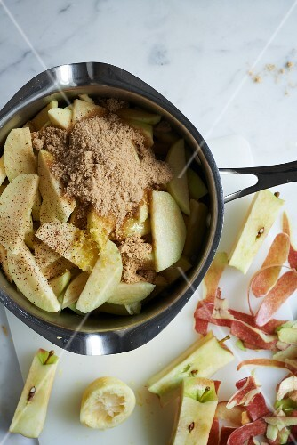 Apple wedges with spices in a pot (ingredients for apple pie)