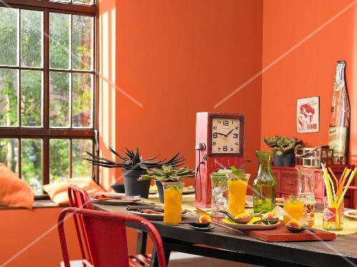 A table laid with mango drinks and appetisers in an orange-painted room