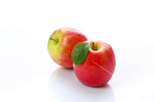 Two red apples on a white surface