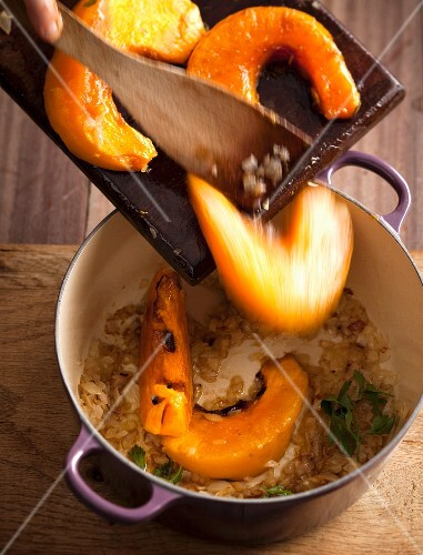 Pumpkin soup being made: oven-roasted pumpkin wedges being added to a pot