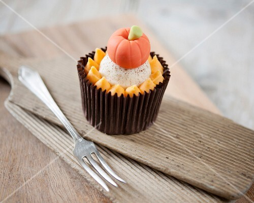 A Pumpkin Spice Cupcake with a Pumpkin Candy on a Green Plate