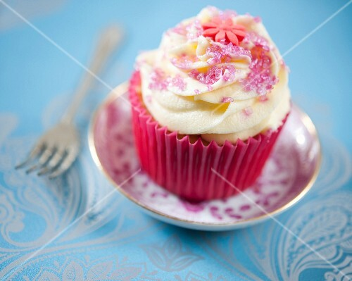 A vanilla cupcake decorated with pink sugar and fondant flowers