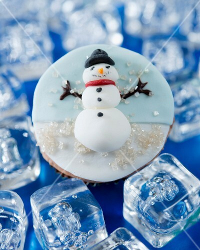 A cupcake decorated with a fondant snowman