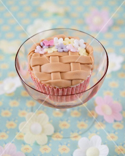 A flower basket cupcake decorated with fondant