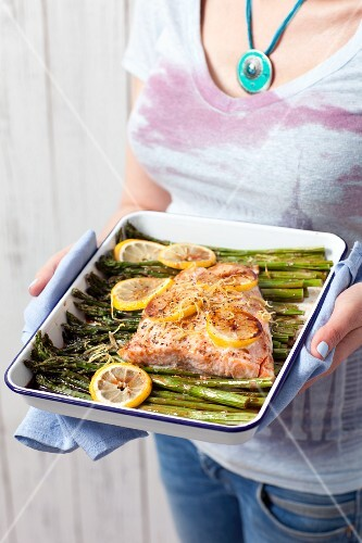 A woman serving baked salmon glazed in soya sauce with asparagus and lemon