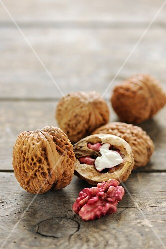 Red walnuts, whole and halved, on a wooden surface