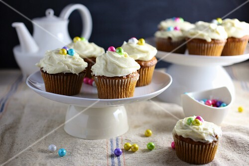 Carrots cupcakes decorated with frosting and colourful sugar pearls