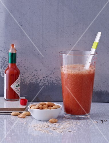 A tomato smoothie with oat bran and Tabasco served with salted almonds