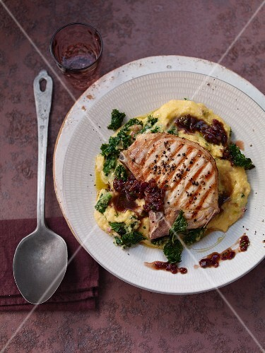 Kale polenta with a pork chop and red onions