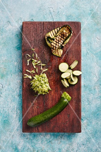 Courgette: whole, sliced, grated and grilled on a wooden board