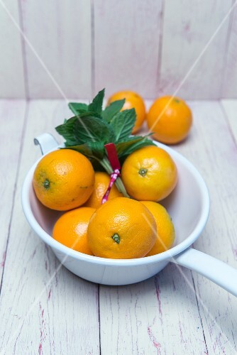 Oranges in an enamel colander with fresh mint