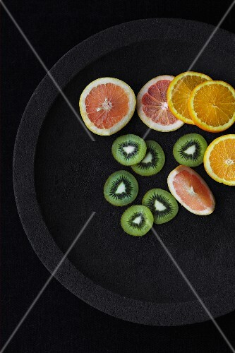 Grapefruit, orange and kiwi slices on a black plate