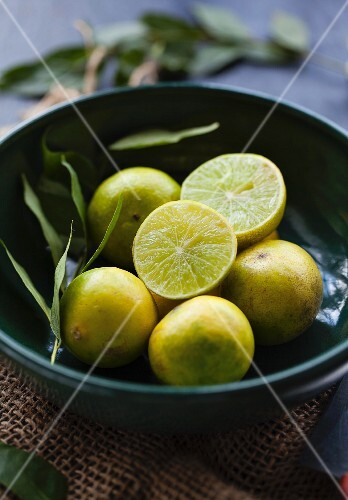 Limes, whole and halved, in a bowl