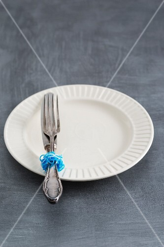 Silver cutlery decorated with rubber bands on a plate