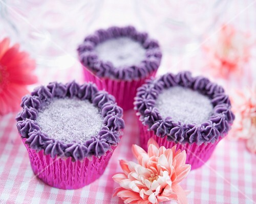 Cupcakes decorated with blackcurrant cream and sugar