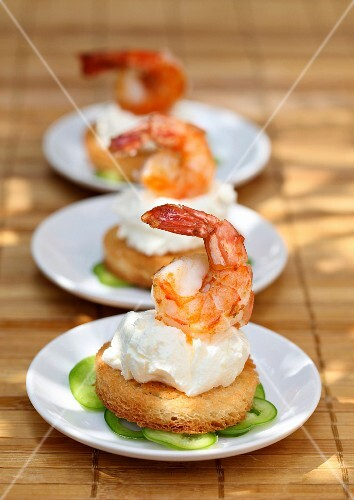 Bread rounds topped with cream cheese and prawns