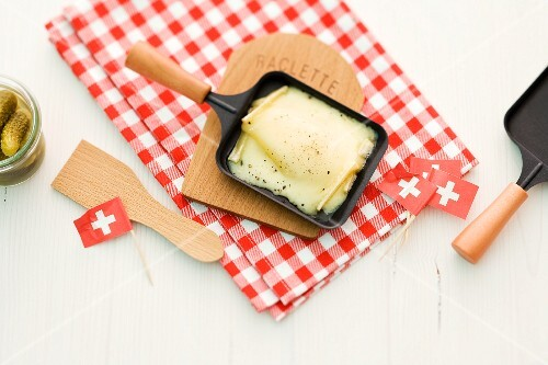 Raclette cheese in pans and black flags