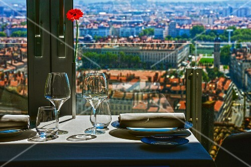 A table laid by a window with a glass balustrade and a view of a city