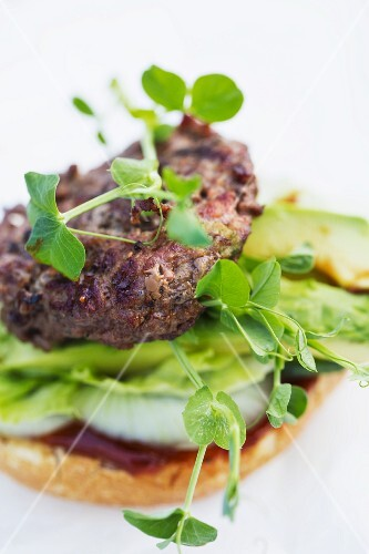 A burger with pea shoots, avocado, lettuce, onions and ketchup