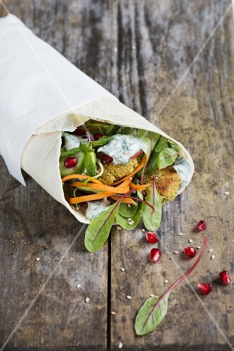 A wrap with falafel, pomegranate seeds, mint, cucumber, beetroot leaves and dill yoghurt