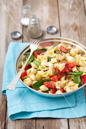 Conchiglie rigate salad with mozzarella, tomatoes, spinach, olives and pesto