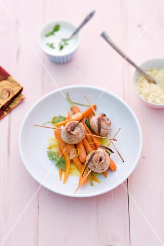 Rabbit skewers on orange carrots