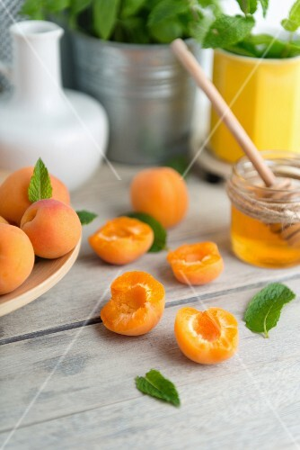 Apricots, whole and halved, on a wooden table with a jar of honey