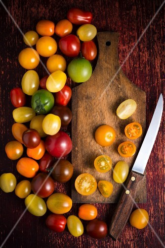 An arrangement of tomatoes with a wooden board and a knife