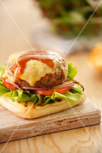 A beefburger with cheese on grilled bread