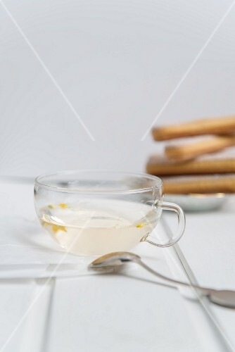 A cup of camomile tea with sponge fingers in the background