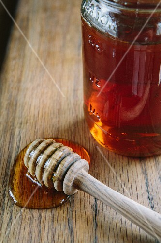 A jar of honey and a honey spoon on a wooden table
